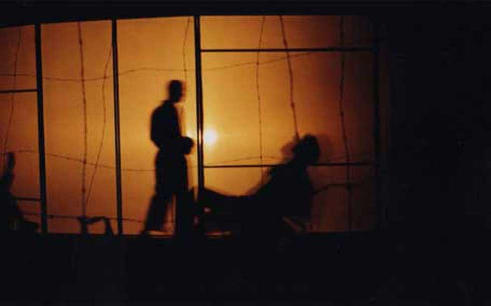 A silhouette of two men behind a glass pane, with one man tied to a chair as the other stands over him intimately.