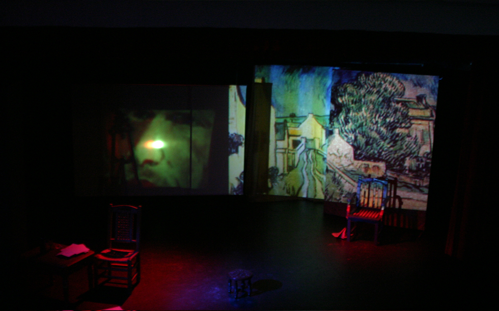 A dim scene in which two paintings of Van Gogh's are projected in the background and two wooden chairs stand in the middle